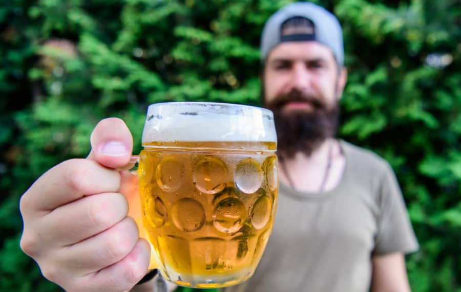 Man holding a jug of home brewed beer